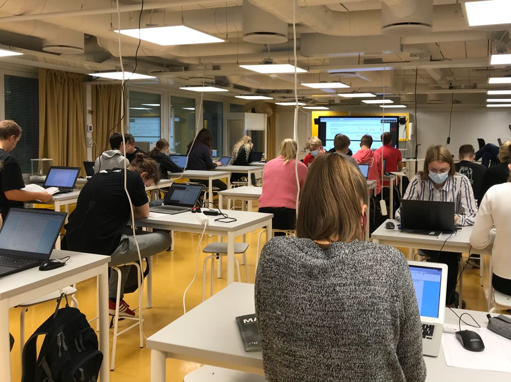 Luokkahuoneellinen lukiolaisia tekemässä kemiakilpailutehtäviä omilla tietokoneillaan