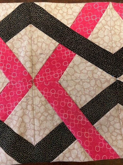 Yksityiskohta tilkkutyöstä, vaalealla pohjalla tummia ja pinkkejä raitoja/kolmioita.