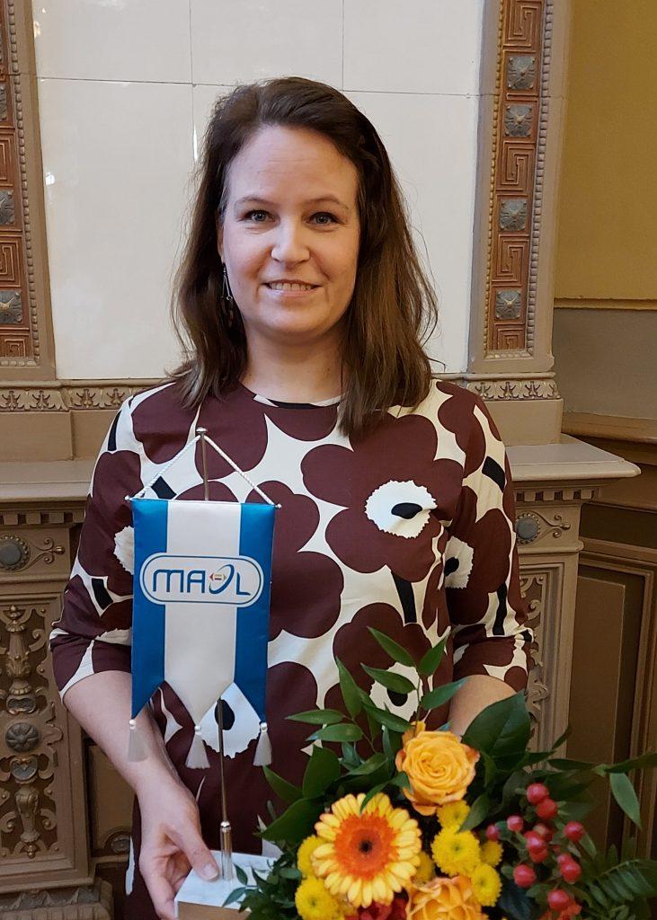 Valokuva Maarit Savolaisesta MAOL-standaarin ja keltaisen kukkakimpun kera
