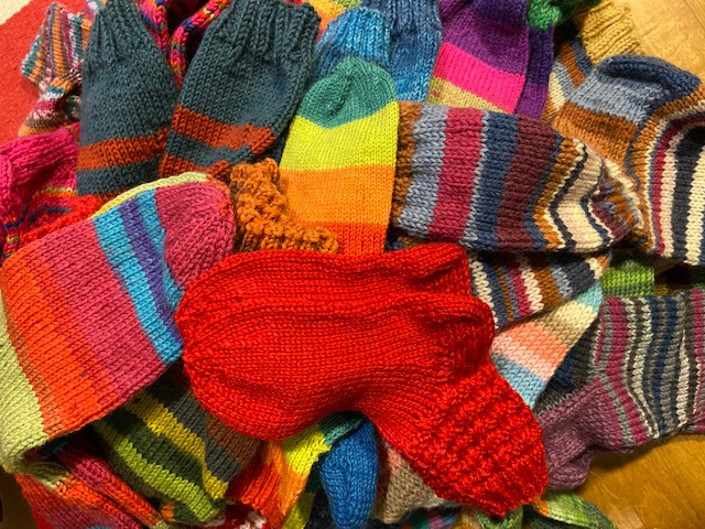 Valokuva, jossa paljon eri värisiä neulottuja villasukkia
